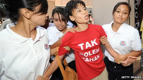 A woman is led away by Singapore police