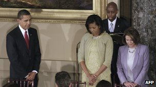 Senate Chaplain Barry Black reads a prayer behind President Barack Obama and First Lady Michelle Obama