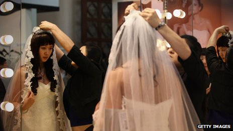 A Chinese woman tries on a wedding dress at the 2012 China Spring Wedding Expo at Beijing Exhibition Center (file photo)
