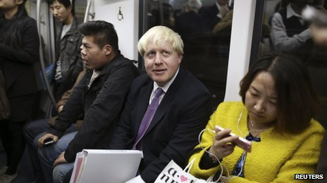 Visiting London Mayor Boris Johnson (C) looks up as he takes a subway in Beijing, 15 October 2013