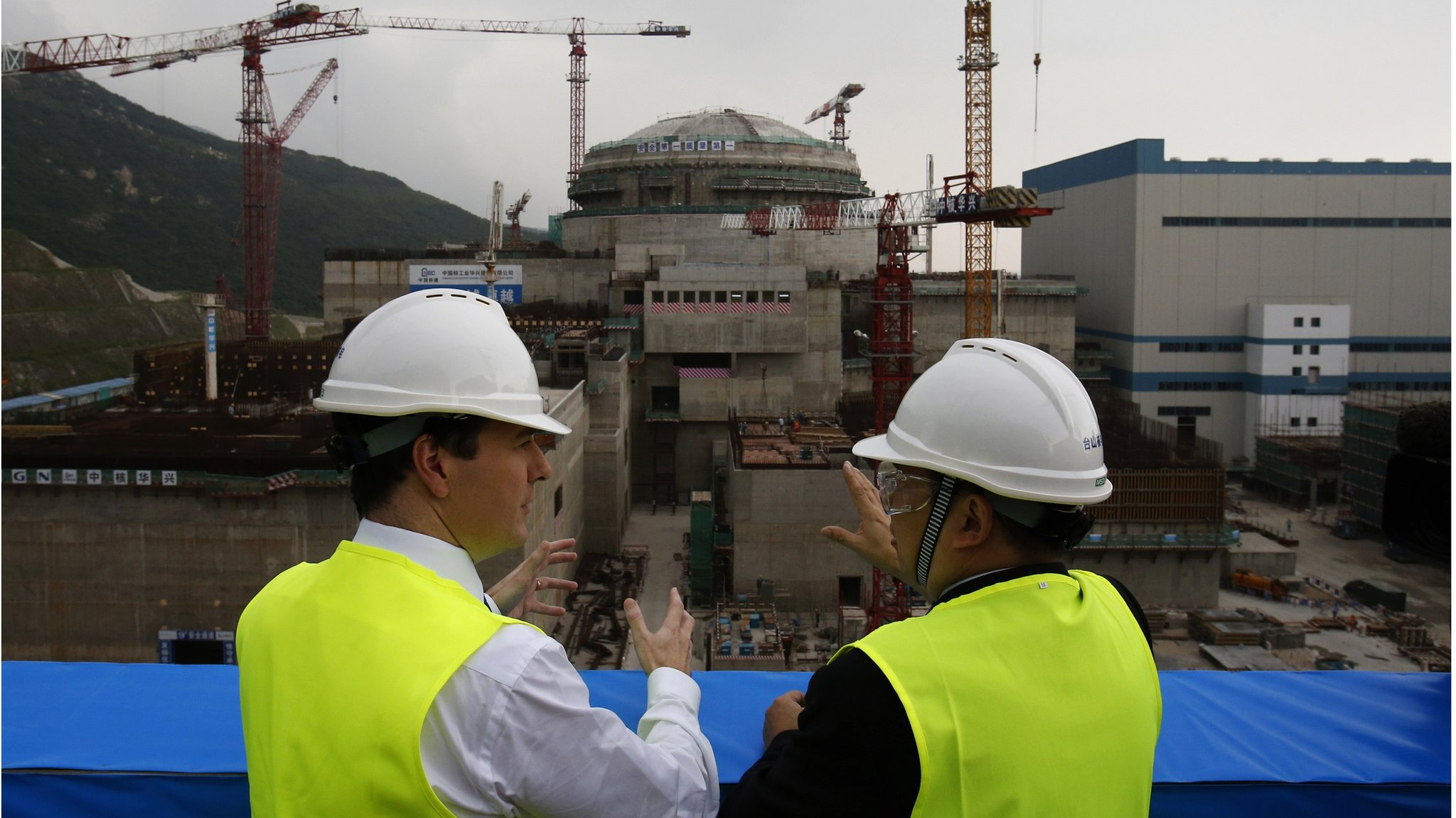 George Osborne (L) talks with Taishan Nuclear Power Joint Venture general manager Guo Liming in front of a nuclear reactor under construction at Taishan, Guangdong province