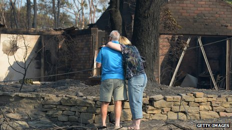 A couple look at a house burnt out by bushfires in Winmalee in Sydney's Blue Mountains on October 18, 2013
