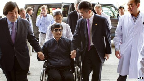 Blind lawyer Chen Guangcheng is wheeled into a hospital by US Ambassador to China Gary Locke, right, and US State Department Legal Advisor Harold Koh, left, in Beijing 2 May 2012