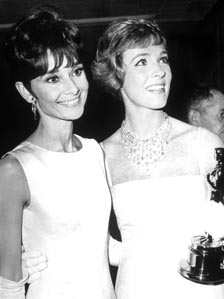 Julie Andrews (right) holds her Oscar while standing with Audrey Hepburn