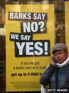 Woman stands by poster advertising loans
