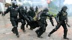 Riot policemen help a colleague who was injured during a protest along the Pan-American Highway