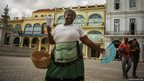 Cuban peanut seller Lysset Perez sings in a street of old Havana, Cuba