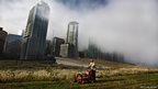Landscaper Graham Reid cuts the grass on top of the Vancouver Convention Centre in Vancouver, British Columbia