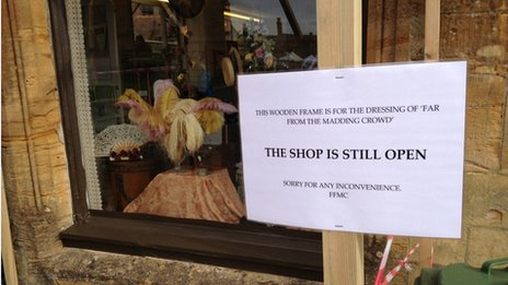 A sign ahead of filming in Sherborne outside Sue Ryder Care charity shop which has had its window display transformed