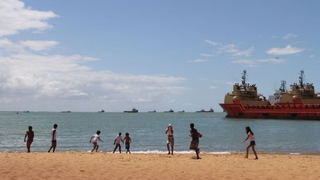 Children play on beach with oil ships in the background