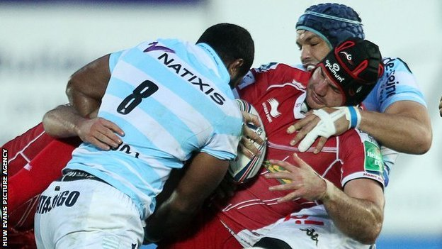 George Earle of Scarlets is tackled by Racing Metro's Sakiusa Matadigo and Luc Ducalcon