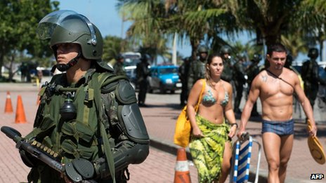 A couple walks past a an officer standing guard in front of the hotel where Brazil's National Petroleum Agency will auction drilling rights to the Libra oil field on 20 October 2013