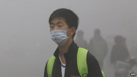 A man wearing a mask walks in heavy smog in Harbin, northeast China's Heilongjiang province, on October 21, 2013