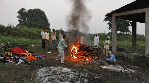 In this Sunday, Oct. 20, 2013 photo, Indian villagers light the pyre of Shiv Bachan, who died after drinking toxic bootleg liquor, on Raj Ghat in Azamgarh district