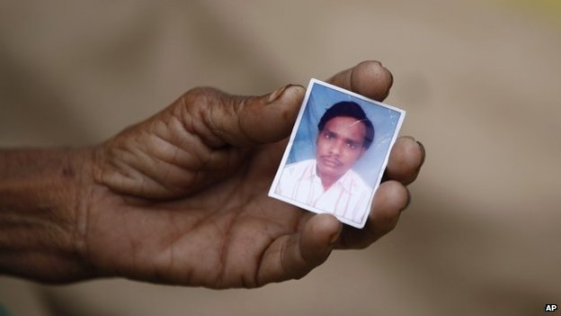 Indian woman Taradevi displays a photograph of her 22-year-old son Umesh Gaur who died after drinking toxic bootleg liquor at Atardiha village in Azamgarh district