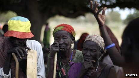 South Sudanese who fled the recent ethnic violence listen as a woman describes the attacks, in Gumuruk, Jonglei State, January 12, 2012