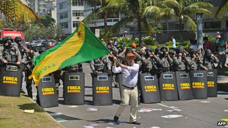 A man waves a flag as security forces guard the site of the Libra auction on 21 October 2013