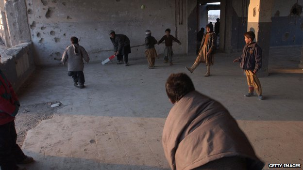 Afghan refugee boys play cricket at a refugee camp in Kabul in 2005