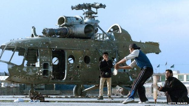 Afghan cricketers take part in a match on a patch of ground in front of a destroyed helicopter
