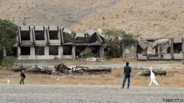 Afghans play cricket in front of a ruined Ministry of Agriculture building in western Kabul in 2009