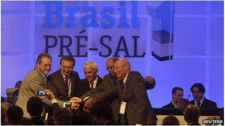 Brazil's Mines and Energy Minister Edison Lobao (second left), with representatives of the winning consortium