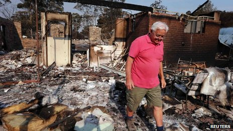 Local resident Alan Seaman walks through the remains of his home in the Blue Mountains suburb of Winmalee, 21 October 2013