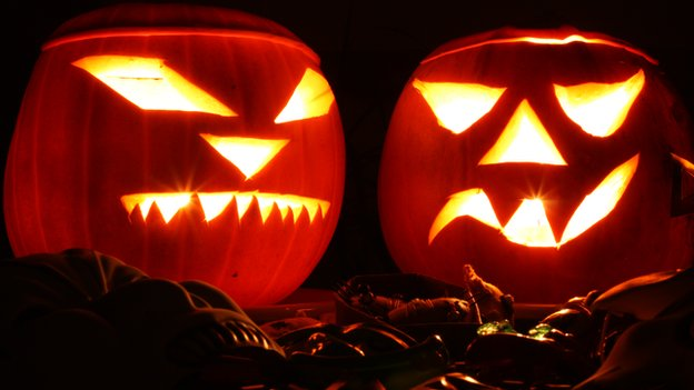 Two lit Jack O Lanterns in a dark background