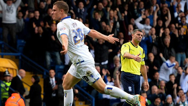 Birmingham captain Paul Robinson looks on dejected as two-goal Leeds striker Matt Smith celebrates at Elland Road