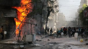 People use buckets to try and extinguish a fire that ignited at a local fuel station in the Bustan al-Qasr neighbourhood of Syria northern city of Aleppo