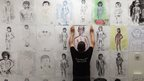 A technician hangs a drawing by a member of the public of Turner Prize-nominated artist David Shrigley's Life Model