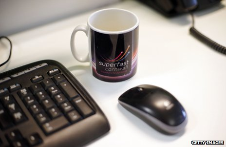 Mug with Superfast Cornwall logo next to a computer