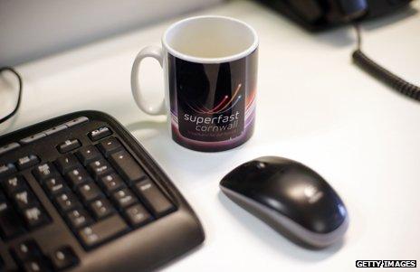 Mug with Superfast Cornwall logo next to a computer
