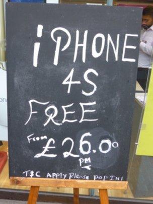 "A shop sign saying ""iPhone 4s free on £26 pm contract"""