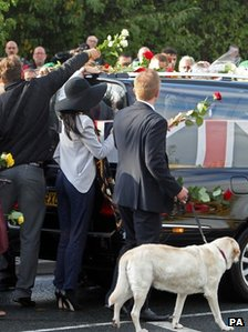 Efrem Brynin, father of L/Cpl James Brynin, holds the soldiers dog on a lead as he lays flowers on the hearse