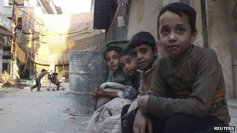 Children sit on a sidewalk of a street in the besieged area of Homs