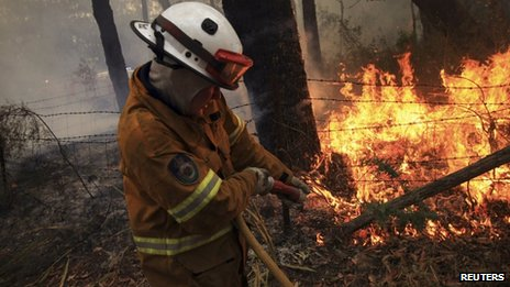 A Rural Fire Service fire-fighter sprays water onto a small fire burning near a home in a Blue Mountains suburb