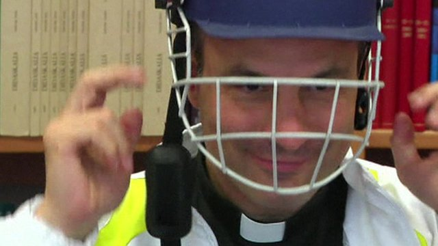 Clergyman in cricket helmet