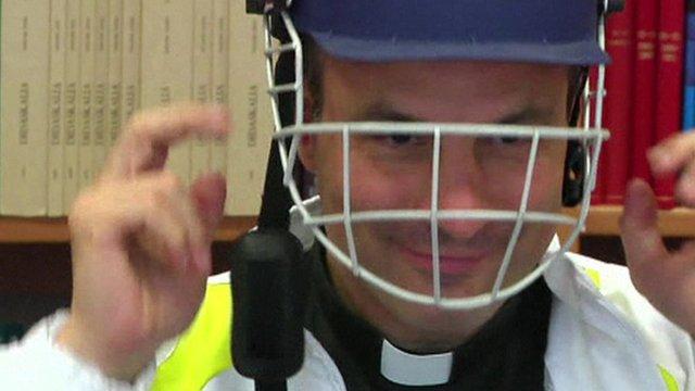 Clergyman in cricket helmet