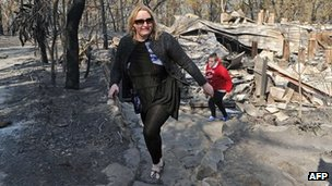 Catherine Hubbard and daughter Amy inspect the remains of their home in Winmalee on 18 October 2013