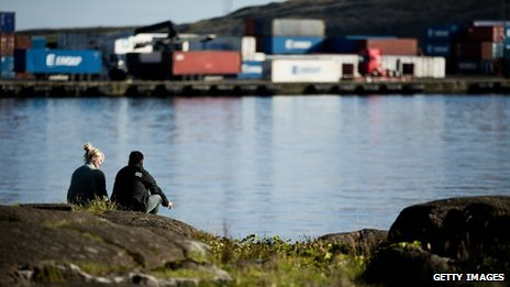 A couple sit overlooking Torshavn harbour in the Faroe Islands