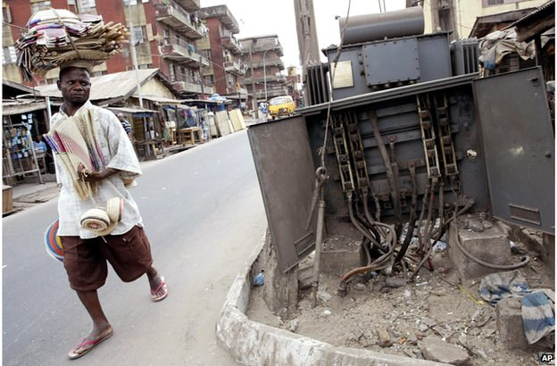 A man walks past a broken electricity transformer in Lagos, Nigeria