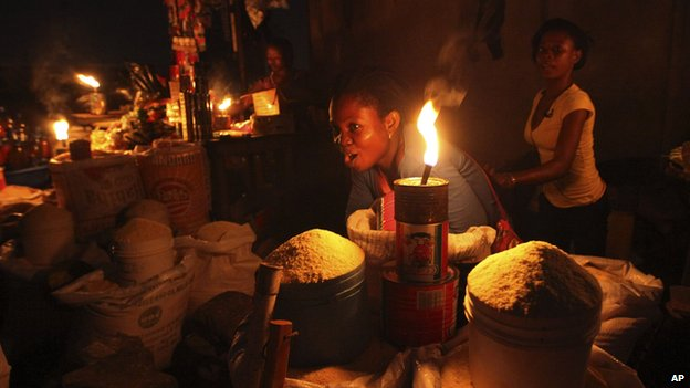 Esther Jacob sells cassava flour by lantern light in Lagos, Nigeria.