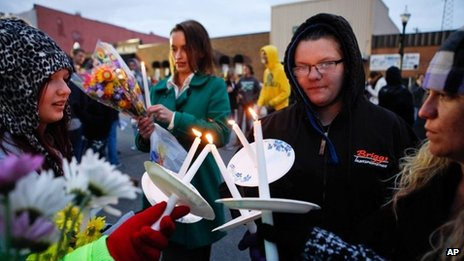 """Sarah Linthacum, right, Maggie Baker, second from right, and Gabrielle Stewart, left, try to keep their candles lit despite the wind during the """"Justice for Daisy"""" rally in Maryville, Missouri 22 October 2013"""