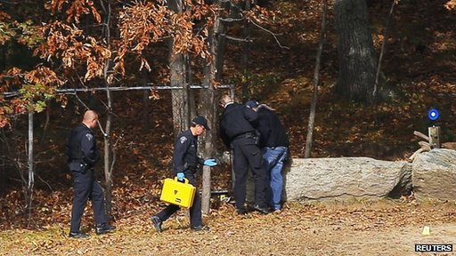 Investigators search the woods behind the high school in Danvers, Massachusetts, on 23 October 2013