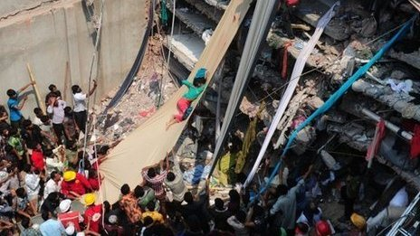 A collapsed building with people climbing fabric