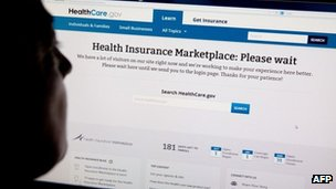 "A woman looks at the HealthCare.gov insurance exchange internet site showing a ""Please wait"" page, in this 1 October 2013 file photo in Washington, DC"