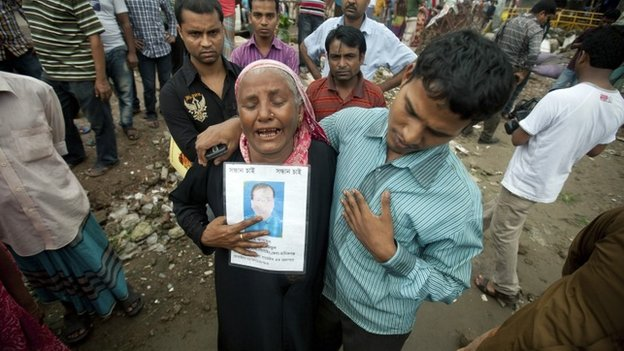 A Bangladeshi woman cries while holding a picture of her son Asadul, who went missing in the Rana Plaza building collapse, as she participates in a protest in Dhaka, Bangladesh, Wednesday, Oct. 23, 2013.