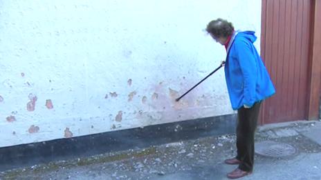 John Larsen shows BBC wall damaged by explosion