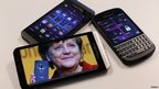 Different BlackBerry smartphones, one showing Chancellor Angela Merkel, featuring high security Secusite software used for governmental communication, are seen at the Secusmart headquarters in Dusseldorf on 24 October 2013
