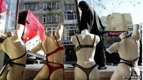 A Turkish Muslim woman walks past an underwear display in Istanbul